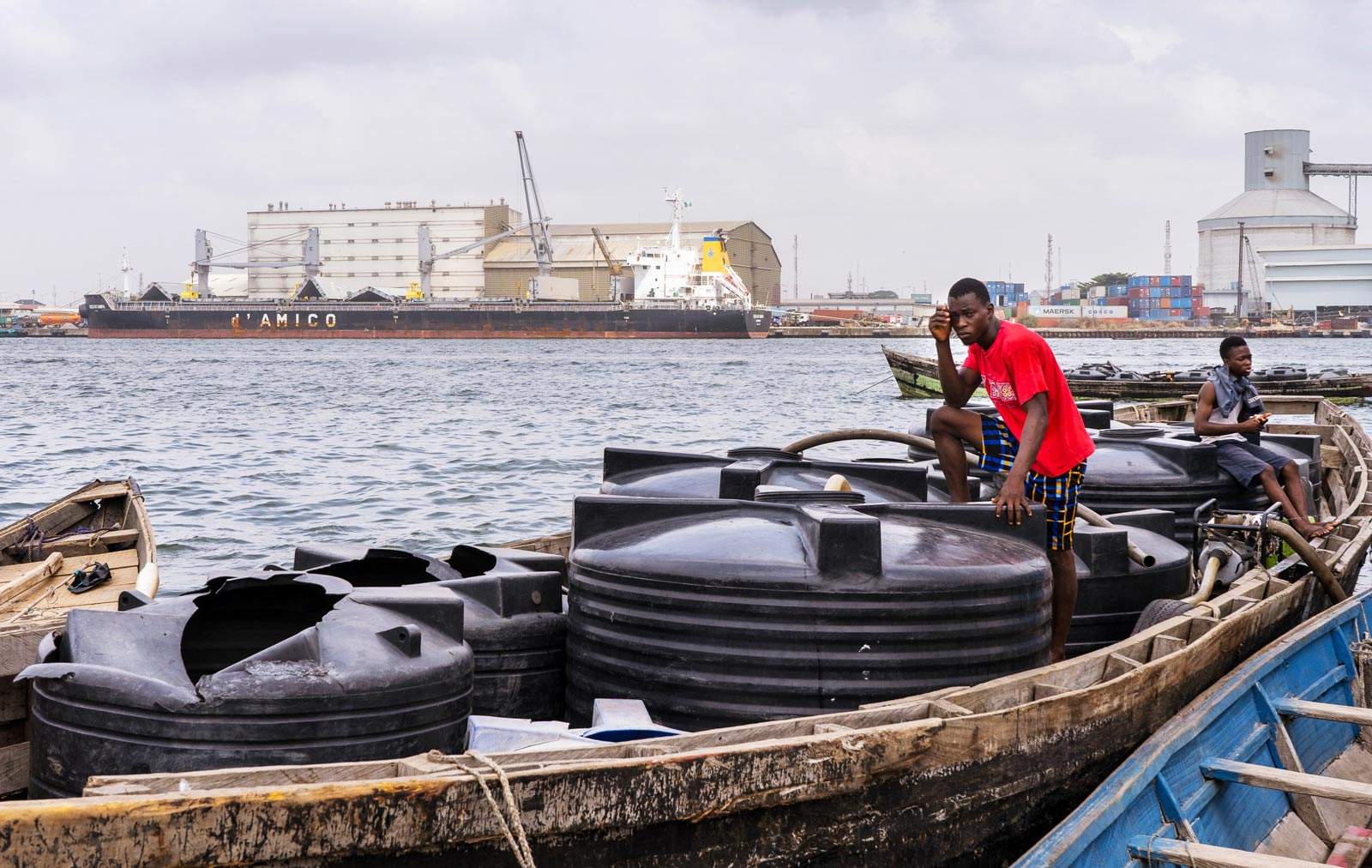 Two young men on a wooden boat at a dock pumping water out of large black water containers.