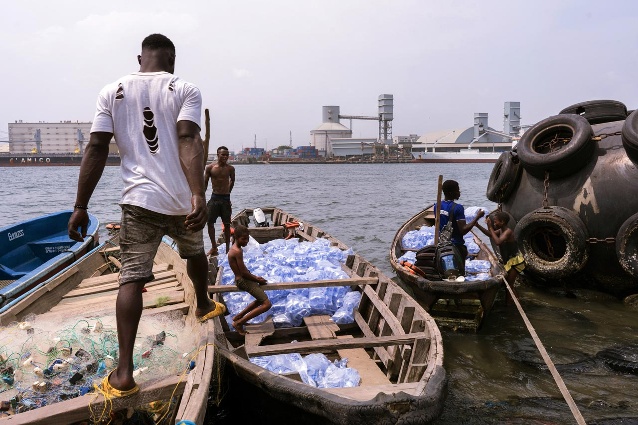 Young men and boys standing and sitting on wooden boats filled with water sachets