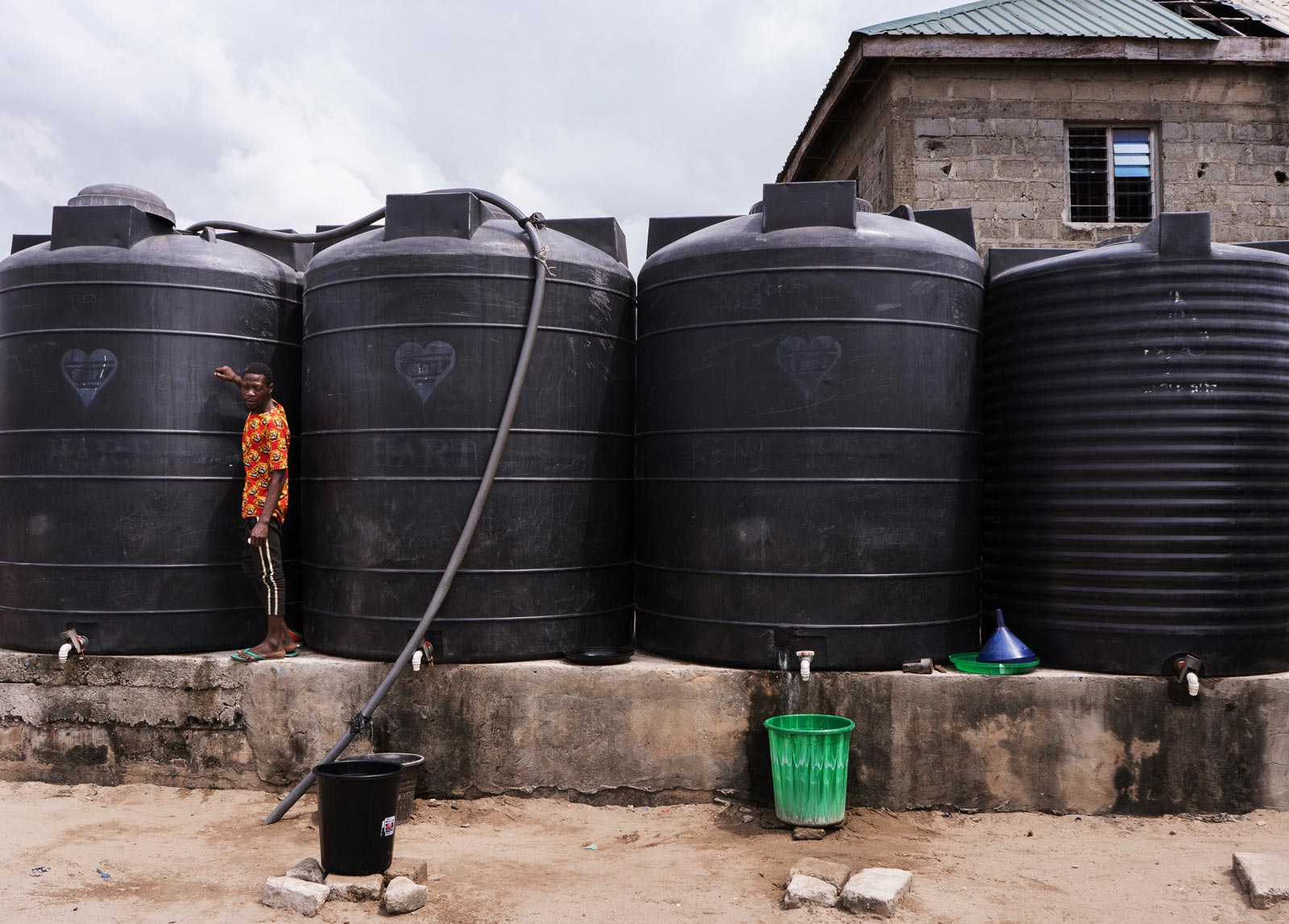 A young man standing in front of 4 large black water tanks that are nearly twice his height.