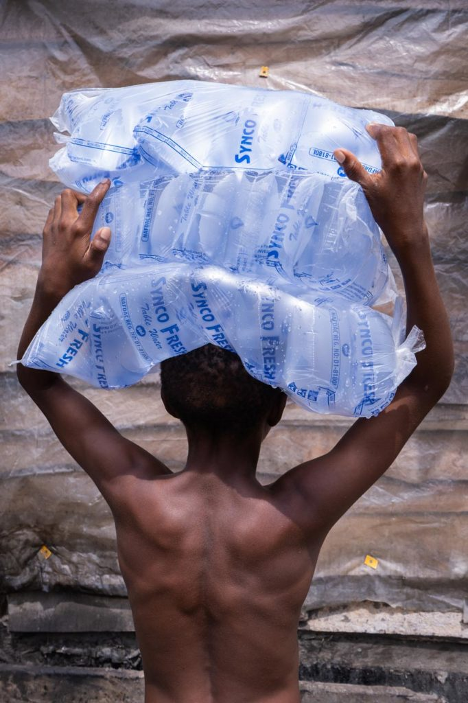 The back of a young boy balancing a pile of water sachets on his head.
