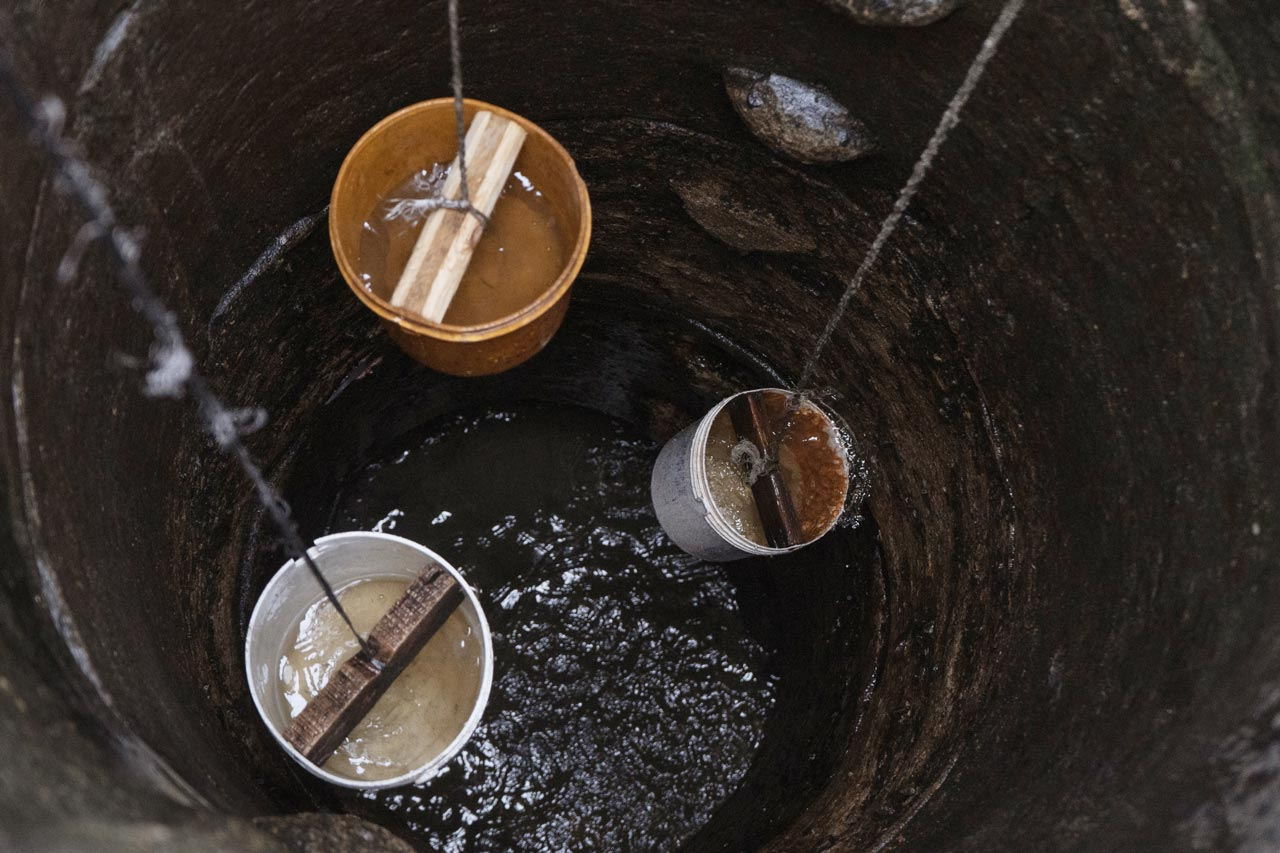 Three buckets full of water being pulled up out of a well by rope