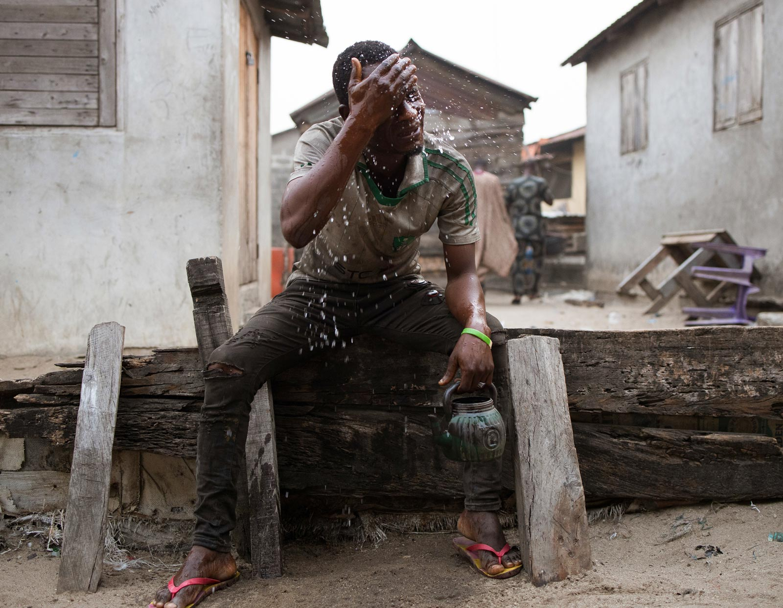 A man sitting down, washes his face using water from a small pot