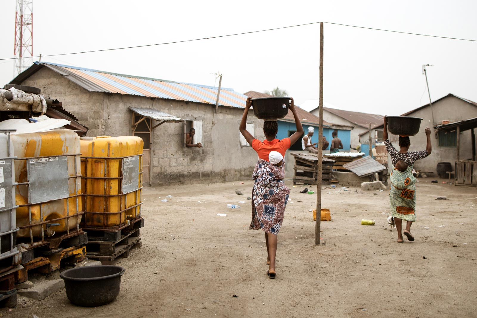 Two women, each carrying a baby on their back, balance buckets filled with water on top of their head as they walk past two large yellow water tanks.