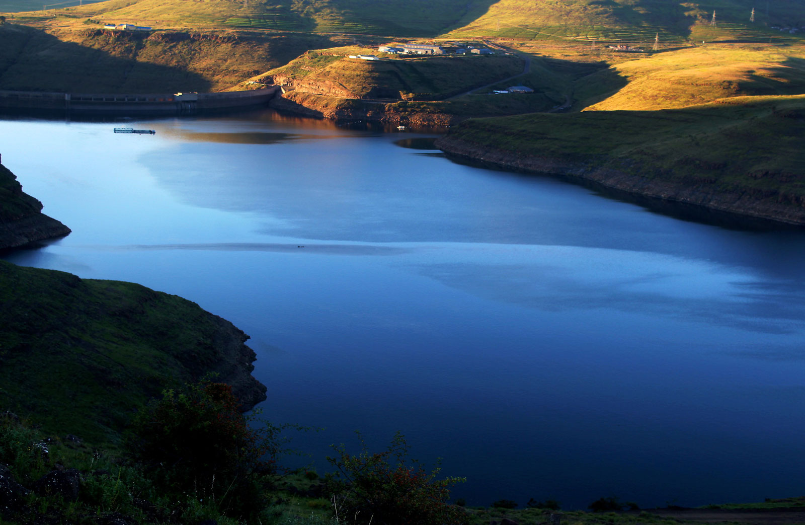 Arial view of a large body of water surrounded by mountain hills. The Katse dam can be see in the far distance with the Lesotho Highlands Development Authority offices above it.