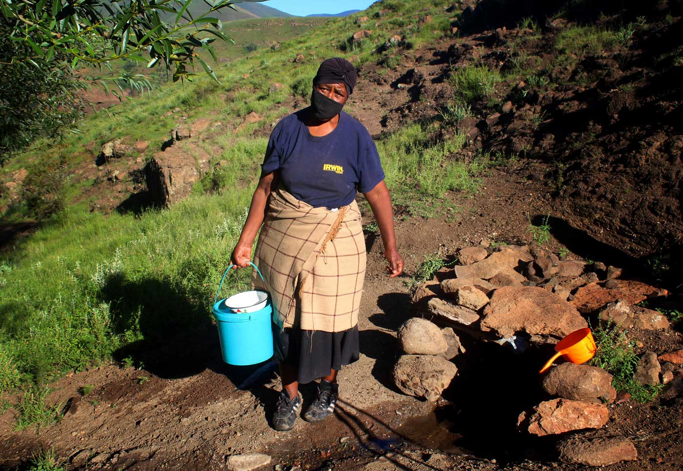 A woman walks along a rock mountain path holding a blue bucket filled with well water