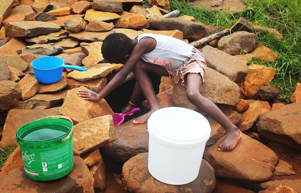 A young girl reaches into a hole surrounded by boulders to scoop water