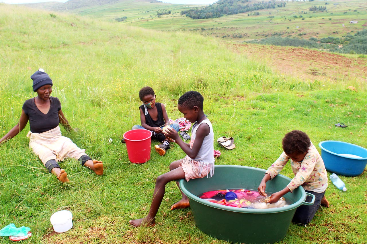 A mother and her young children sit outside in the grass washing their laundry in a large green tub
