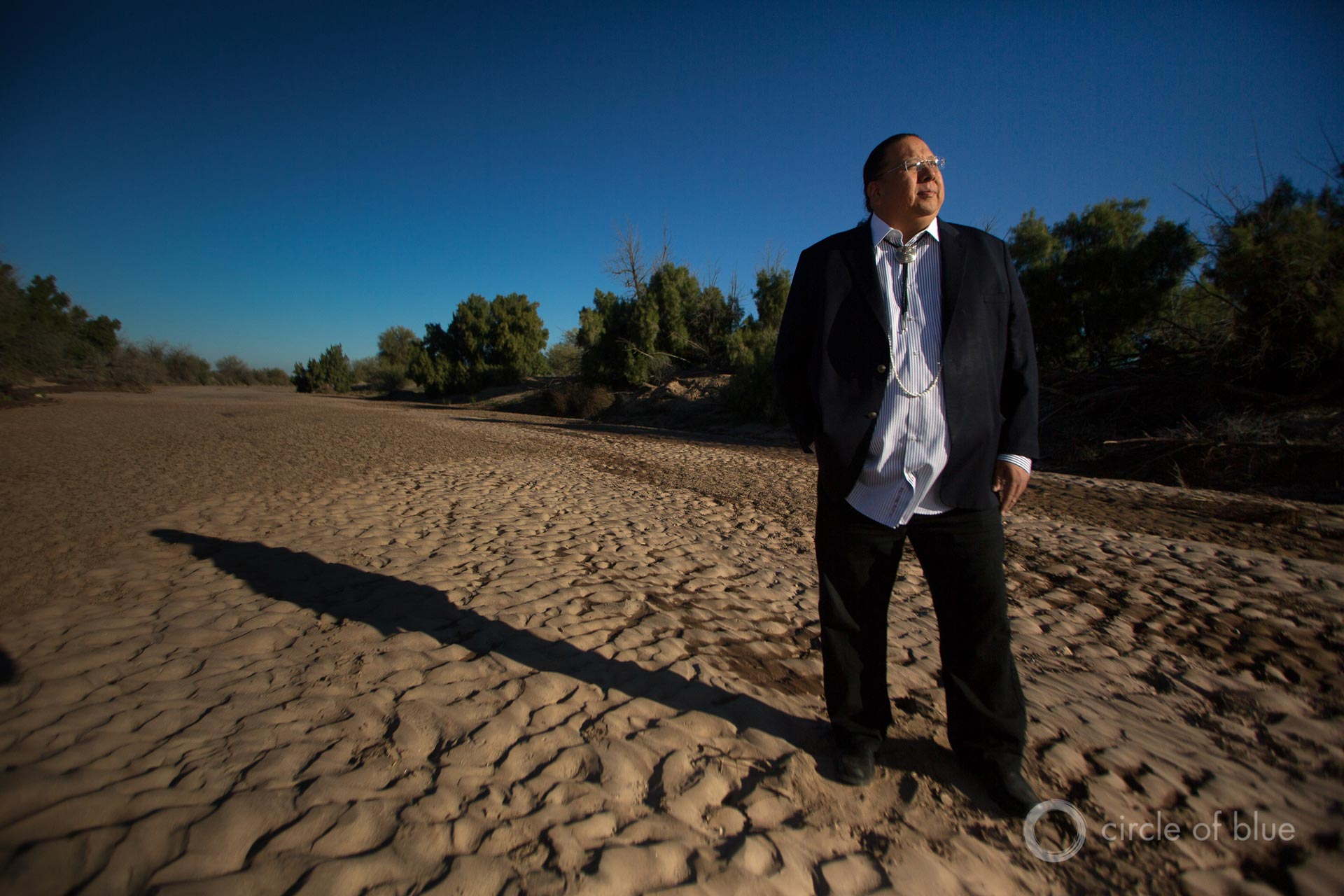 Governor Stephen Roe Lewis, leader of the Gila River Indian Community, stands in the dry bed of the Gila River, outside of Sacaton, Arizona.