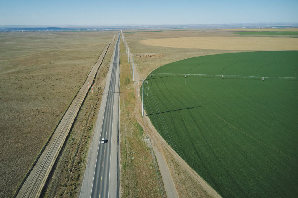 Aerial view of Bombing Range Road diving a disused US Navy bombing range and large areas of irrigated green land.