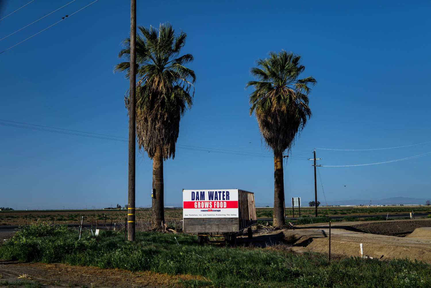 Political signs on State Route 43 just outside the city limits of Corcoran, CA support the construction of more dams.