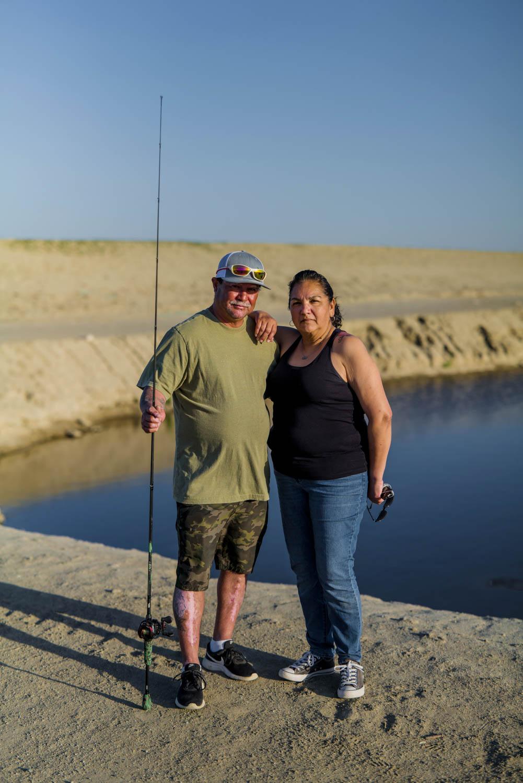 Lifelong Corcoran, CA residents David Quintero and his girlfriend, Christina Escobedo, fish on the Corcoran Cross Creek Levee.