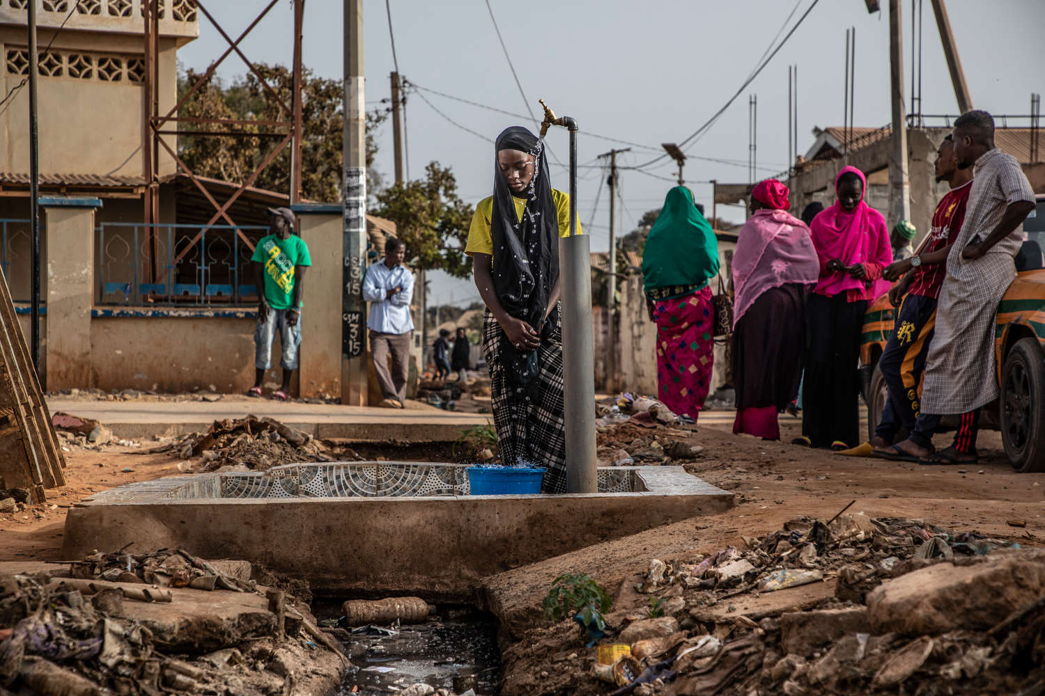 Isatou Jammeh collects water from a community tap that sits directly on an open sewage drain.