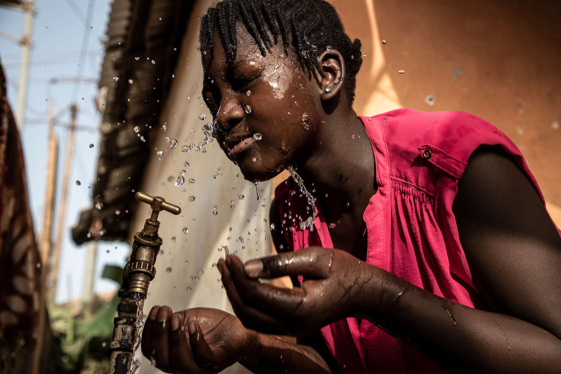 Ya Nima Jaiteh, 14, washes her face at a tap in her family's compound.